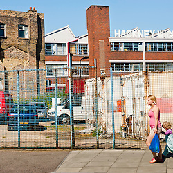 London, UK - 23 July 2012: A local woman with a child walks past the Hackney Wick sign in Hackney Wick, very close to the London 2012 Olympic Park. The area, once a major  manufacturing center in the UK, is now a mix of old warehouses converted into artist's studio and industrial yards attracting now both tourists and Olympic staff members