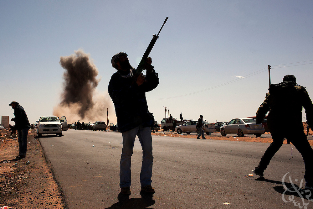 A Libyan rebel fighter points his gun towards a government fighter jet flying overhead seconds after it bombed a rebel checkpoint position March 07, 2011 in Ras Lanouf, Libya. For more than 2 weeks rebels in Eastern Libya have been battling pro-Qadaffi forces, seeking to topple the nearly 42 year old dictatorship of Col Moammar el-Qadaffi.