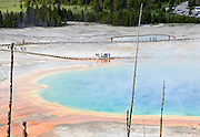 People viewing colorful Grand Prismatic Spring on a boardwalk in Yellowstone National Park in Wyoming. The Grand Prismatic Spring in Yellowstone National Park is the largest hot spring in the United States, and the third largest in the world, next to those in New Zealand.The spring is approximately 250 by 300 feet (75 by 91 m) in size and is 160 feet (49 meters) deep.