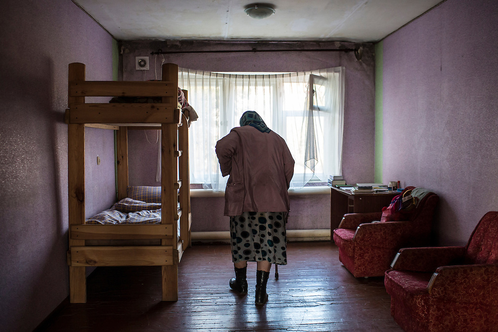 Nadezda Panasyk, 75, in her temporary accomodations provided by the Donetsk Protestant Church on Friday, October 17, 2014 in Donetsk, Ukraine. Panasyk's apartment  building is used by fighters for the Donetsk People's Republic to coordinate efforts to gain control of the Donetsk airport, one of the most heavily contested ongoing battles of the war in Eastern Ukraine. Daily shelling of the neighborhood made it unsafe for her to stay any longer, but with no family or money she had nowhere else to go. Photo by Brendan Hoffman, Freelance