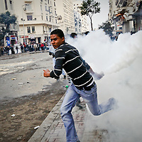 A demonstrator prepares to throw a tear gas canister at riot police during clashes in downtown Cairo, Egypt. January 2011.