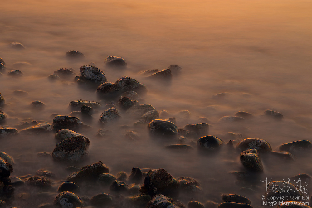 A long exposure blurs the action of Puget Sound waves as they crash around the beach rocks at Mukilteo, Washington at sunset.