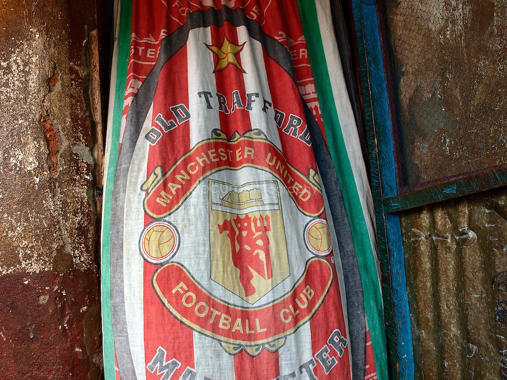 An Old Trafford curtain in the doorway of a fan, Kroobay, Freetown, Sierra Leone