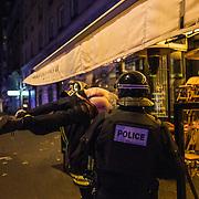 Des policiers s'occupent d'un blessé, le 13 novembre 2015 boulevard des Filles du Calvaire à Paris, à proximité de la salle du Bataclan dans laquelle se déroule au même moment une attaque terroriste.