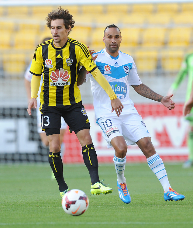Phoenix's Albert Riera, left, plays in front of Melbourne Victory's Archie Thompson in the A-League football match at Westpac Stadium, Wellington, New Zealand, Saturday, Januray 18, 2014. Credit:SNPA / Ross Setford