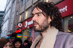 Oxford Street, London, December 5th 2014. Actor and Comdeian turned political activist Russel Brand visits several big brands'  stores including Boots, Apple and Vodafone in London accusing them of dodging tax whilst those most in need of benefits are facing cuts and increased hardship. A leaflet being distributed by him claims £14 billion is lost every year, through tax avoidance and loopholes exploited by big business. PICTURED: Russel Brand outside Vodafone's Oxford Street branch.