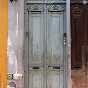 """An old wood double door is painted light blue in San Telmo barrio, the heart of old Buenos Aires, Argentina, South America. Admire well-preserved old buildings in San Telmo (""""Saint Pedro González Telmo""""), the oldest barrio (neighborhood) of Buenos Aires."""