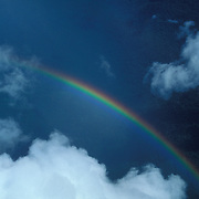 Venezuela, aerial of rainbow over rainforest in Guyana Highlands, with cumulus clouds.