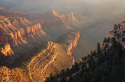 The warm light of sunrise reaches the depths of the Grand Canyon.