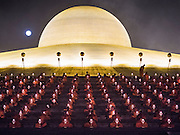 "11 FEBRUARY 2016 - KHLONG LUANG, PATHUM THANI, THAILAND:  The full moon rises above the temple while Buddhist monks pray in their seats on the pagoda during the Makha Bucha Day service at Wat Phra Dhammakaya.  Makha Bucha Day is a public holiday in Cambodia, Laos, Myanmar and Thailand. Many people go to the temple to perform merit-making activities on Makha Bucha Day, which marks four important events in Buddhism: 1,250 disciples came to see the Buddha without being summoned, all of them were Arhantas, or Enlightened Ones, and all were ordained by the Buddha himself. The Buddha gave those Arhantas the principles of Buddhism. In Thailand, this teaching has been dubbed the ""Heart of Buddhism."" Wat Phra Dhammakaya is the center of the Dhammakaya Movement, a Buddhist sect founded in the 1970s and led by Phra Dhammachayo. Makha Bucha Day is one of the most important holy days on the Thai Buddhist calender.     PHOTO BY JACK KURTZ"