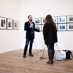 London, UK - 8 October 2012: curator Simon Baker interviewed beside pictures by Daido Moriyama. The exhibition examine the relationship between the work of William Klein (b.1928) and that of Daido Moriyama (b.1938). Taking as its central theme the cities of New York and Tokyo, the show explores both artists' celebrated depictions of modern urban life.