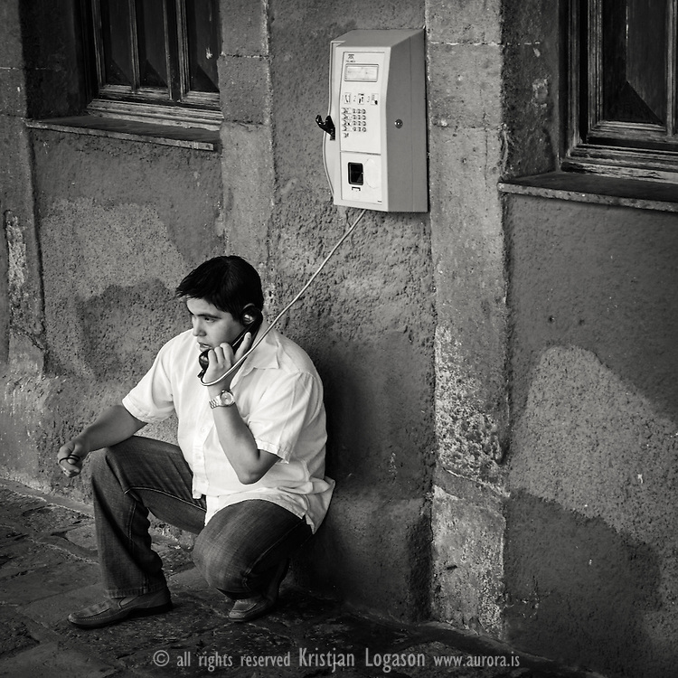 Young man talking on the phone at the square in San miguell de allende