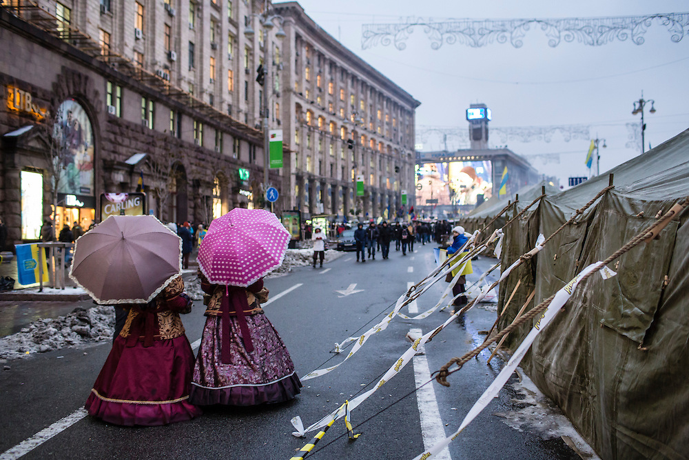 KIEV, UKRAINE - DECEMBER 13: Two women selling candy while dressed in Victorian outfits walk toward Independence Square on December 13, 2013 in Kiev, Ukraine. Thousands of people have been protesting against the government since a decision by Ukrainian president Viktor Yanukovych to suspend a trade and partnership agreement with the European Union in favor of incentives from Russia. (Photo by Brendan Hoffman/Getty Images)