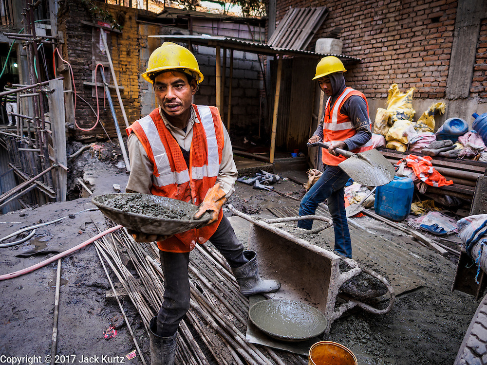 05 MARCH 2017 - KATHMANDU, NEPAL: A worker hands a tray of cement to a coworker on a construction site that is rebuilding a building near Kathmandu's Durbar Square destroyed in the 2015 earthquake Much of Kathmandu is now a construction site because of rebuilding  two years after the earthquake of 25 April 2015 that devastated Nepal. In some villages in the Kathmandu valley workers are working by hand to remove ruble and dig out destroyed buildings. About 9,000 people were killed and another 22,000 injured by the earthquake. The epicenter of the earthquake was east of the Gorka district.    PHOTO BY JACK KURTZ