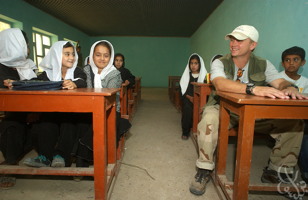U.S. Army Cpt. Bill Mandrick (R), of the 489th Civil Affairs Battalion from Knoxville, TN, jokes with students at the Bi-Bi Khadija Tol Kobra girls school June 8, 2002 in Kunduz, Afghanistan. Mandrick and others from the 489th oversaw the reconstruction and equipping of the school, which educates some 4,000 girls, as part of the ongoing Operation Enduring Freedom.