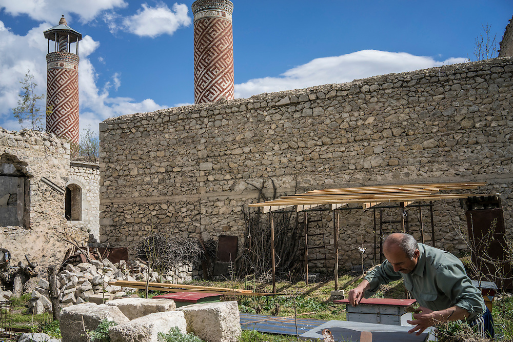 SHUSHI, NAGORNO-KARABAKH - APRIL 19: Slava Petrosyan, 50, tends to the bees he keeps in his garden next to the Lower Mosque on April 19, 2015 in Shushi, Nagorno-Karabakh. Petrosyan, a veteran of the war between Armenia and Azerbaijan over Nagorno-Karabakh, was advised by a doctor to eat more honey after he was wounded in the fighting, and has kept bees as a result. Since signing a ceasefire in a war with Azerbaijan in 1994, Nagorno-Karabakh, officially part of Azerbaijan, has functioned as a self-declared independent republic and de facto part of Armenia, with hostilities along the line of contact between Nagorno-Karabakh and Azerbaijan occasionally flaring up and causing casualties. (Photo by Brendan Hoffman/Getty Images) *** Local Caption ***