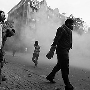 Egyptian protestors walk through clouds of tear gas fired by security forces during ongoing demonstrations November 20, 2011 near Tahrir square in central Cairo, Egypt.  Protestors demanding the transition of power from military to civilian control clashed with Egyptian security forces for a second straight day in central Cairo, with hundreds injured and at least 11 protestors killed.  (Photo by Scott Nelson).