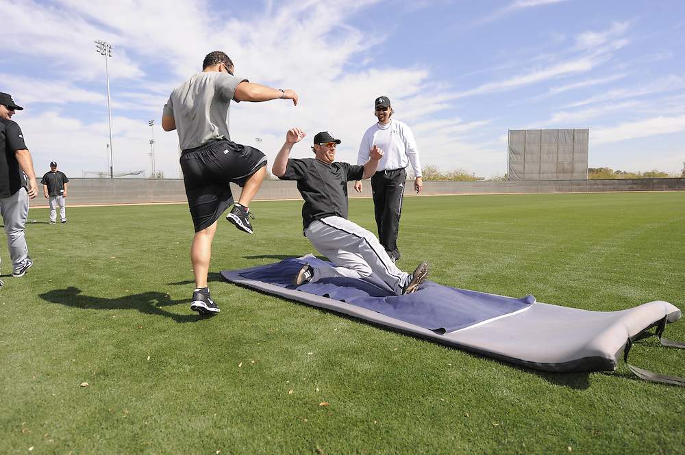 GLENDALE, AZ - FEBRUARY 25:  Adam Dunn #32 of the Chicago White Sox practices sliding as strength coaches Allen Thomas (L) and Dale Torborg look on during a spring training workout on February 25, 2011 at Camelback Ranch in Glendale, Arizona. (Photo by Ron Vesely)