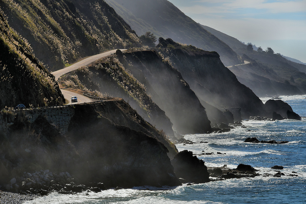 Fog Along Cliffs, Road and Crashing Surf on Big Sur Coast, California<br /> Big Sur was one of the most inaccessible coastlines in the U.S until the 90 mile Carmel-San Simeon Highway was finished in 1937.  It took prison laborers 18 years to construct this coastal road.  Today, you can enjoy its unspoiled natural beauty as California Route 1 twists and turns between the Santa Lucia Mountains and the crashing surf of the Pacific Ocean.