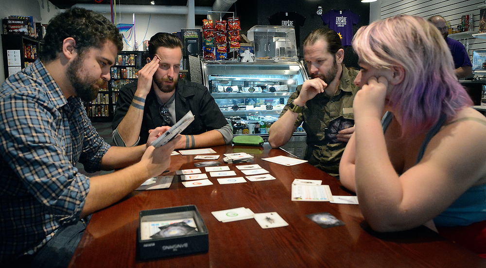 jt042617c/spec sec/jim thompson/ left to right- Andres Gonzales looks through the instructions  of the new game they are learning to play as Victor Hall, Just Phulin(not his real name) and Violet Replicon wait their turn.  Wednesday April 26, 2017. (Jim Thompson/Albuquerque Journal)