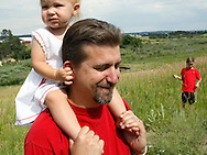 Priscilla Jeub, 1 holds onto her father Chris' ears in their yard in Monument, Colorado July 19, 2009. Quiverfull believers Wendy and Chris Jeub have 15 children and would be happy to have more if God wills it they say. REUTERS/Rick Wilking (UNITED STATES)