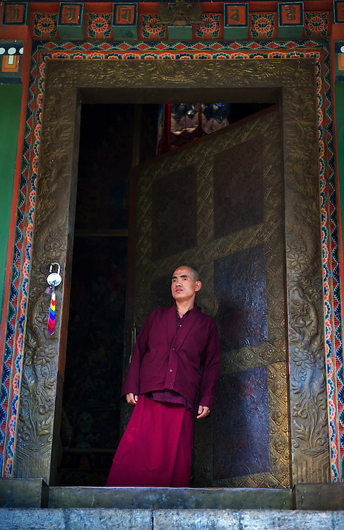 A monk at the doorway to a temple in Bhutan.