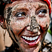 SHOT 6/4/11 2:57:23 PM - Elizabeth Tapper of Denver, Co. flashes a mud covered smile after the Mud Run at the 10th Annual Teva Mountain Games in Vail, Co. Professional and amateur outdoor adventure athletes from the Vail Valley and around the world will converge upon the mountains and rivers of Vail to compete in eight sports and 23 disciplines including: x-country, freeride, slopestyle and road cycling, freestyle, 8-Ball, sprint and extreme kayaking, raft cross, World Cup Bouldering, stand up paddle sprint and surf cross, as well as trail, mud and road running, dog comps and the GNC Ultimate Mountain Challenge.. (Photo by Marc Piscotty / © 2010)
