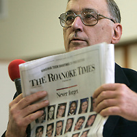 Professor John Cundiff, a Virginia Tech professor, holds up a newspaper with photos of the shooting victims to point out which of his students was killed in Blacksburg, Virginia April 22, 2007. Cundiff was speaking at the Sunday church service at Tried-Stone Christian Center. REUTERS/Rick Wilking (UNITED STATES)