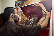 Celebrated young pakistani artist Asim Butt on a journey of political graffiti through Pakistan during the summer of 2009..Asim works on a recent painting in his studio in karach.