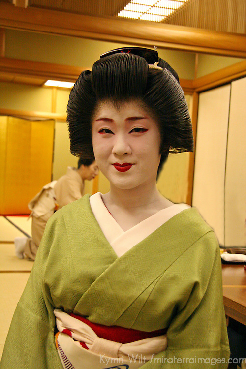 Asia, Japan, Kyoto. A geisha at a private dinner entertaining guests.