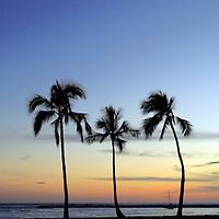 The moon rises as the sun sets over Waikiki Beach.