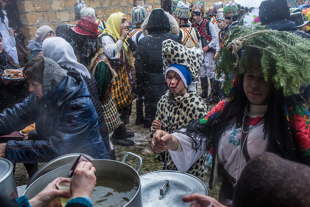 Women pass out cups of hot bouillon and other traditional foods such as stuffed cabbage rolls during a break for lunch in celebrations of the Malanka Festival to eat lunch on Thursday, January 14, 2016 in Krasnoilsk, Ukraine. The annual celebrations, which consist of costumed villagers going in a group from house to house singing, playing music, and performing skits, began the previous sundown, went all night, and will last until evening.