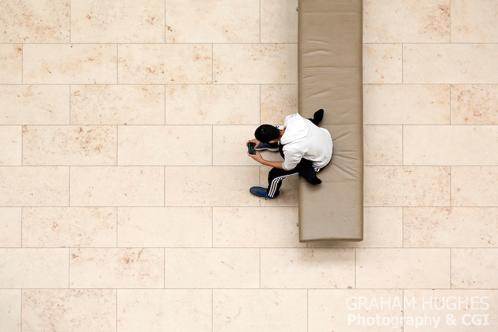 Boy Sitting On Museum Bench With Phone, Game In Hands