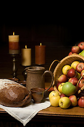 Still life with apples, bread, candles and pottery