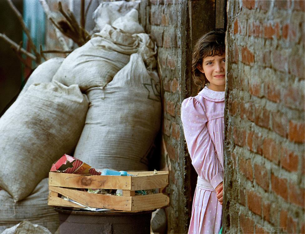 SAN ANTONIO LOS RANCHOS, CHALATENANGO, EL SALVADOR- MAY 2000: A young girl peers out the doorway of her home in San Antonio Los Ranchos.  The ciudad (town) of San Antonio Los Ranchos in Department de Chalatenango, El Salvador was a Frente Farabundo Martí para la Liberación Nacional controlled town.  (Photo by Robert Falcetti). .