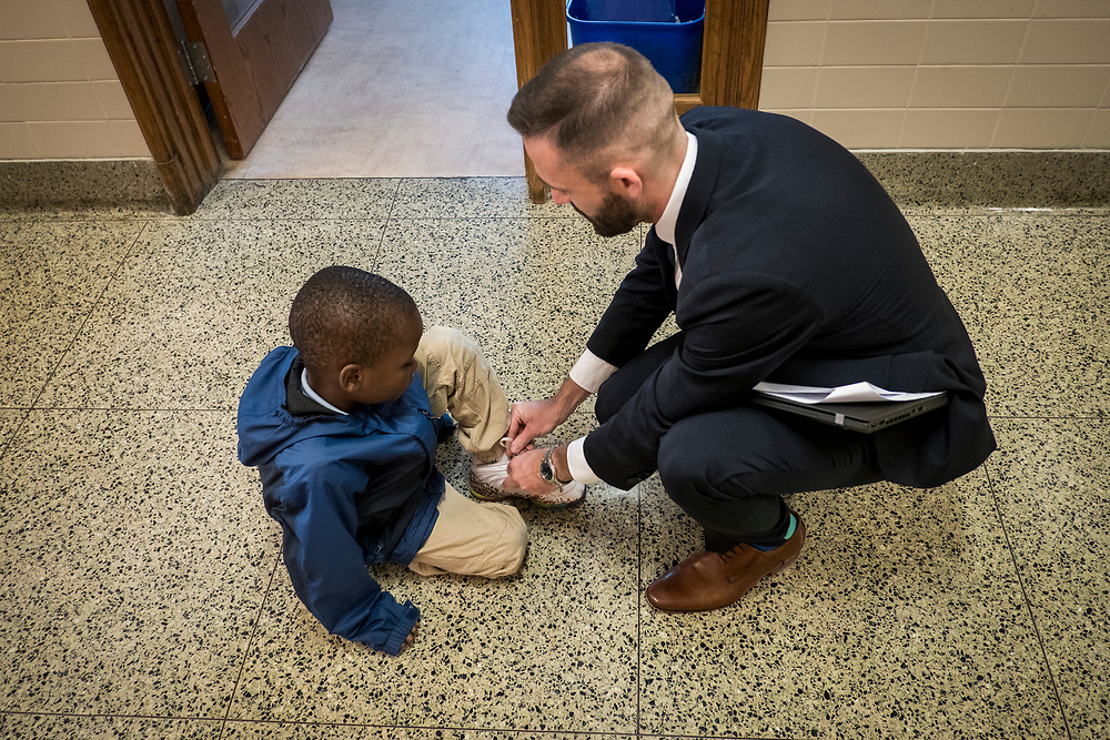 Eric Christopher, Leap ELA Instructional Coach at Turner Elementary School in Washington, D.C., helps a student tie his shoe in the hallway on Wednesday, May 4, 2017.
