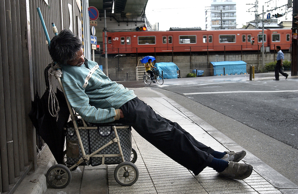 One of many of Osaka's homeless sleeps under a railway bridge out of the rain between Tennoji and Shinimamiya Stations in Kamagasaki District. 20/06/02..©David Dare Parker/AsiaWorks Photography
