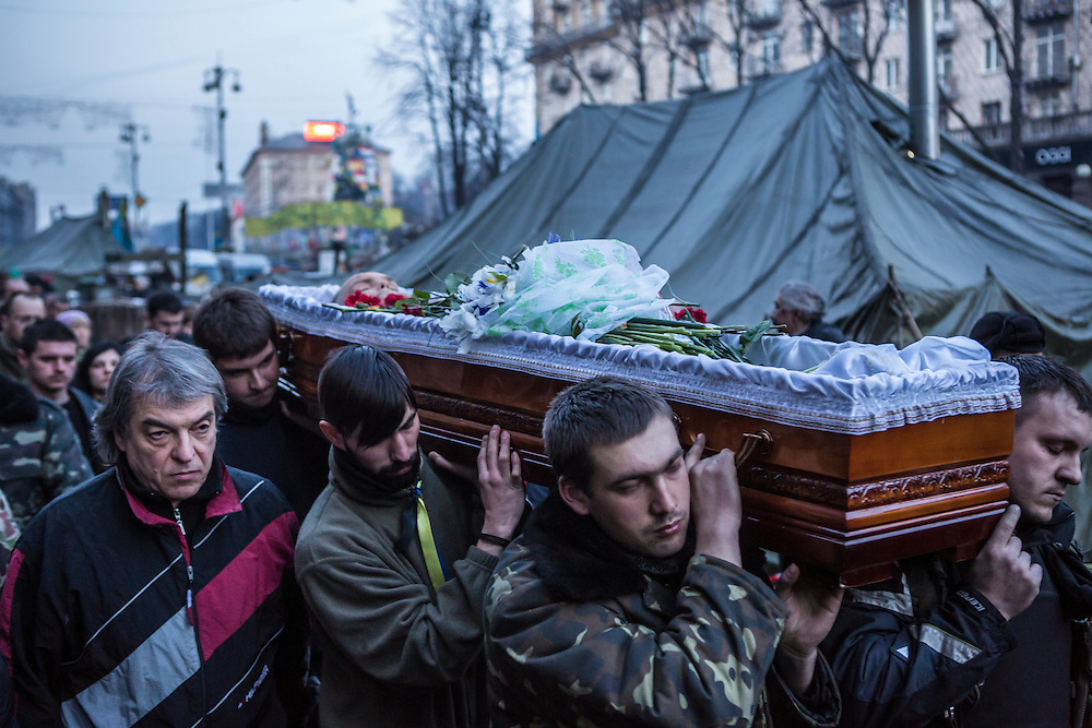 KIEV, UKRAINE - FEBRUARY 21: The body of Ustim Holodnyuk, 19, who was killed in fighting between anti-government protesters and police, is carried from Independence Square on February 21, 2014 in Kiev, Ukraine. After a week that saw new levels of violence, with dozens killed, opposition and government representatives reached an agreement intended to resolve the crisis. (Photo by Brendan Hoffman/Getty Images) *** Local Caption ***