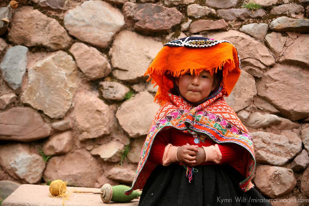 Americas, South America; Peru, Cusco. A young Peruvian girl learns the family trade of weaving at Awana Kancha.