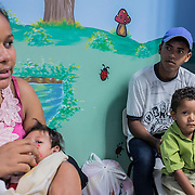 Jayane (17), her daughter with severe microcephaly Nathally (6 months), her husband Daniel (20) and their other son David (3) waiting for their turn at the rehabilitation center at FAV (Fundação Atilio Valente) in Recife, Pernambuco. Jayane and her husband Daniel are indigenous people of the tribe Xukuru do Ororubá from the interior of Pernambuco state, 350 km from Recife. They don't have a house in Recife so they have to travel more than three hours in order to come to the rehabilitation center every week