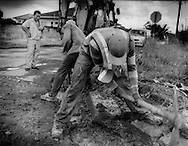 "A Chinese supervisor from China Dalian International oversees two Surinamese Creole workers doing manual road repair in the capital city of Paramaribo, Suriname.  From a communique leaked by Wikileaks, the US Embassy says, ""The Chinese company Dalian (China Dalian International) is very active in road building in Suriname.  Some ministries reportedly prefer to work with the Chinese in order to receive what is perceived as complications-free cash-flow, while others worry about long-term effects (and political liabilities) of such hasty deals.  The Chinese, meanwhile, have their eyes on Surname's rich natural resources, particularly wood"".  China Dalian International recently paved the road that roughly follows the Suriname River straight inland to the jungle outpost Atjoni, which many believed was the first step to build a road to Brazil opening up the interior.  In a conversation with a Da Ware Tijd Newspaper staff writer, Eleazer Pross, a Memoranda of Understanding signed on 2 December 2010 between the government of Suriname and the Peoples Republic of China was voted down in the legislature here.  China had offered US$ 6 billion in projects to build a railroad, or road (it was never clearly stated to the public which it was) and a deep sea harbor in Paramaribo.  This would have opened up one of the world's largest untouched rainforest wildernesses to rapid encroachment along the path of the railroad/road.  Eleazer Pross said today, ?the Chinese demands were basically too much.  They basically demanded the entire (interior) forest (for logging) as compensation for building the road?.  ..China Dalian claims on its website to have rehabilitated or constructed over 500 km of road in and around Paramaribo."