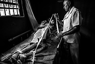 A nurse restrains Raúl Martínez, a paranoid schizophrenic who also suffers from depression during an episode when he lost control and was at risk of hurting himself. He did not have all of the medicines that he required to keep him stable, because of the shortages.