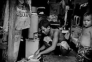 Father prepares a meal in his makeshift house that sits on a sidewalk on Radial Road 10, which runs parallel to the port just a few meters above sea level in Tondo and exceedingly vulnerable to flooding.  <br /> Most of the vast slums of Manila's Tondo District in the Philippines are not only just a few meters above sea level but, in a seismically active area, are built on reclaimed land beside Manila Bay.  <br /> <br /> On Maplecroft's Climate Change Vulnerability Index, Manila ranks as the world's second most vulnerable city to climate change.  Manila's Tondo is Manila's district most vulnerable to climate change-induced sea rises, storm surges from increasingly strong typhoons and earthquake trigger tsunami.  It has a population density of nearly 78,000 people per square km (202,800 ppl/sq mi), according to a 2009 Cornell University report.  (Note: Manhattan has a population density of 26,939/km2 [69,771/sq mi].)