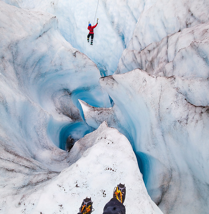 Ethan Welty tip toes to the edge of a deep moulin to photograph client Mack F. Pennington ice climbing (for his first time ever) on a day trip with St. Elias Alpine Guides to the Root Glacier in Wrangell-St. Elias National Park, Alaska.