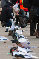 London, December 10th 2014. The shoes of hundreds of victims who died in Ireland, North and South during the Troubles are lined up opposite Downing Street as families demand that a proper investigation into over 3,600 deaths and 40,000 injuries on all sides, sets the truth free. PICTURED: A man reads the stories attached to the shoes reminding us of how people died in the violence.