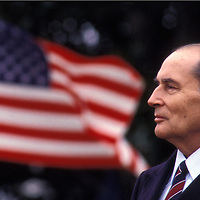 1984 French President Francois Mitterand in front of American flag during a visit to the White House.