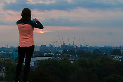 Primrose Hill, London, September 22nd 2016. A jogger stops to take a picture on Primrose Hill as the autumn equinox sun rises over London . &copy;Paul Davey<br /> FOR LICENCING CONTACT: Paul Davey +44 (0) 7966 016 296 paul@pauldaveycreative.co.uk