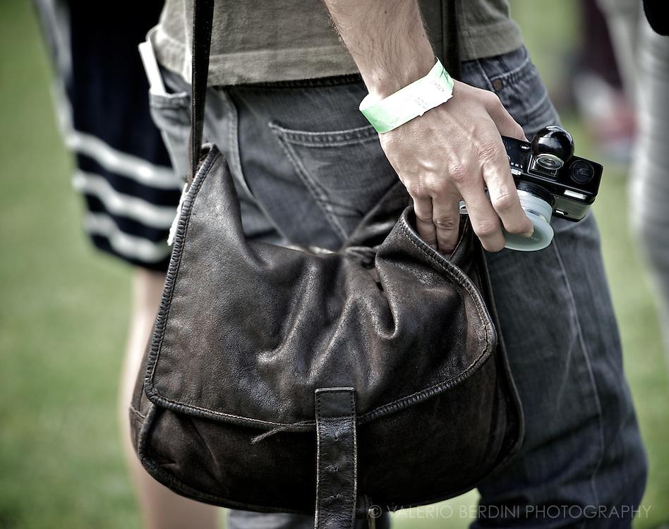 Vintage leather bag. Cheap film camera. Wristband.