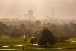 Primrose Hill, London, October 30th. The sun begins to break through as mist shrouds London's skyline, as dog walkers and fitness fanatics enjoy Primrose Hill. Pictured: London's skyline towers over the mist rising at Regent's Park.