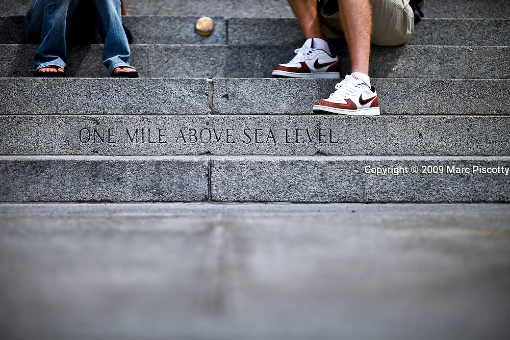 "SHOT 8/13/09 2:04:39 PM - The words ""One mile above sea level"" mark the spot orginally thought to be 5,280 feet (or one mile) above sea level on the steps of the Colorado State Capitol. The official elevation of Denver is measured outside the west entrance to the building, where the fifteenth step is engraved with the words ""One Mile Above Sea Level."" From this step, around dusk, a magnificent view of the sun setting behind the Rocky Mountains can be taken-in at 5,280 feet (1,609 m). A second mile high marker was set in the 18th step in 1969 when Colorado State University students resurveyed the elevation. Finally, in 2003, an even more accurate measurement was made with modern means and the 13th step was identified as being one mile (1.6 km) high where a 3rd marker was installed. Colfax Avenue is the main street that runs east and west through the Denver-Aurora metropolitan area in Colorado. As U.S. Highway 40, it was one of two principal highways serving Denver before the Interstate Highway System was constructed. In the local street system, it lies 15 blocks north of the zero point (Ellsworth Avenue, one block south of 1st Avenue). For that reason it would normally be known as ""15th Avenue"" but the street was named for the 19th-century politician Schuyler Colfax. On the east it passes through the city of Aurora, then Denver, and on the west, through Lakewood and the southern part of Golden. Colloquially, the arterial is referred to simply as ""Colfax"", a name that has become associated with prostitution, crime, and a dense concentration of liquor stores and inexpensive bars. Playboy magazine once called Colfax ""the longest, wickedest street in America."" However, such activities are actually isolated to short stretches of the 26-mile (42 km) length of the street. Periodically, Colfax undergoes redevelopment by the municipalities along its course that bring in new housing, trendy businesses and restaurants. Some say that these new developments detract from the chara"